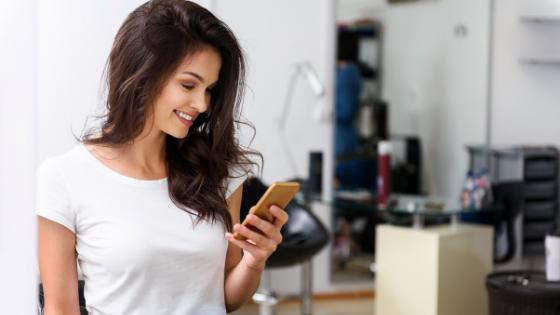 Woman looking at phone - social media for salons