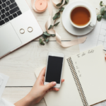 Woman writing to-do list, flatlay, phone and laptop