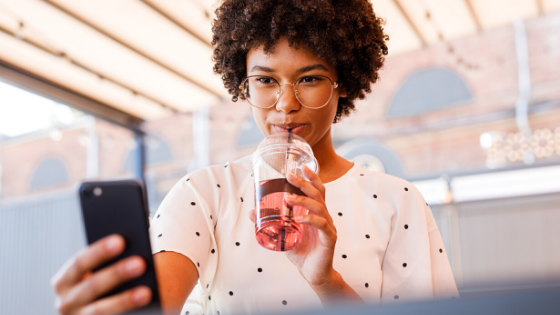 woman drinking a drink and checking her phone - social media, engagement