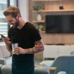 man smiling at his phone - social media engagement