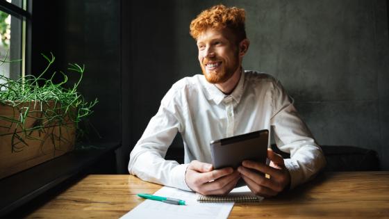 Man smiling using tablet - social media, shops