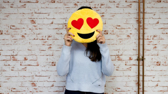 Woman holding heart eyes emoji cushion - South Coast Social