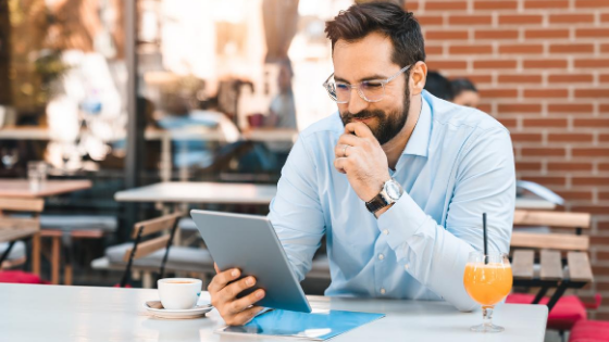 Businessman sat having coffee outdoors looking at a tablet
