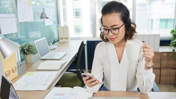 Businesswoman checking phone at desk